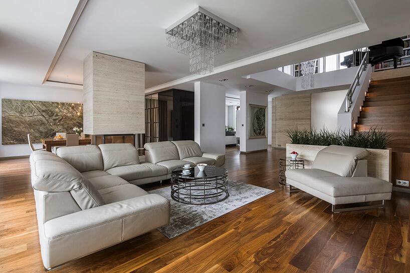 przestronny elegancki salon wdomu piękną drewnianą podłogą zjasnym skórzanym eleganckim zestawem wypoczynkowym