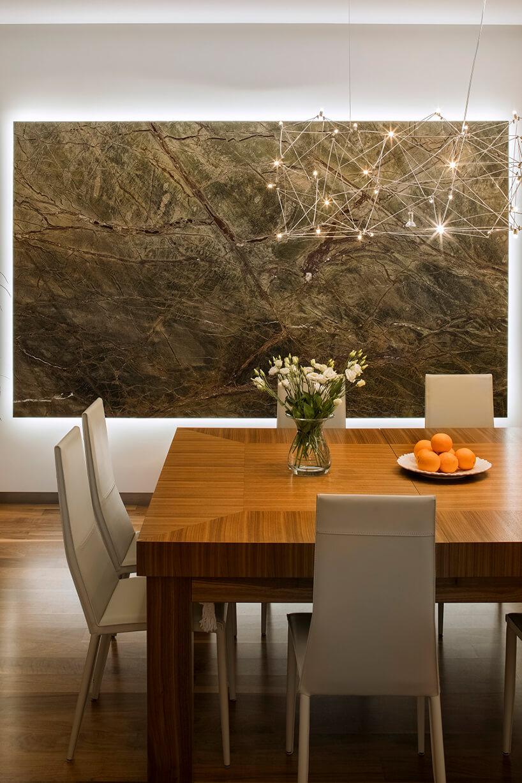 piekny drewniany stół zbeżowymi krzesłami pod delikatnym żyrandolem na tle kamiennej płyty na ścianie