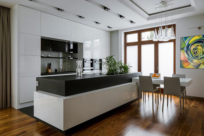 elegancka biała kuchnia zwyspą zczarną górą zmałym białym stolikiem zczterema krzesłami