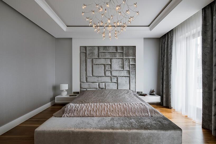 elegancka biało szara sypialnia zdużym łóżkiem ze srebrną narzuta pod wyjątkowym żyrandolem