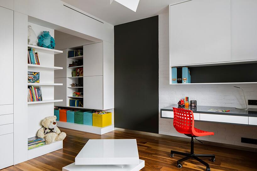 biały pokój starszego dziecka zdrewnianą podłogą zczarnym kawałkiem ściany