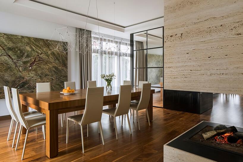 elegancka jadalnia dużego domu zdużym drewnianym stołem ijasnymi krzesłami pod delikatnym żyrandolem