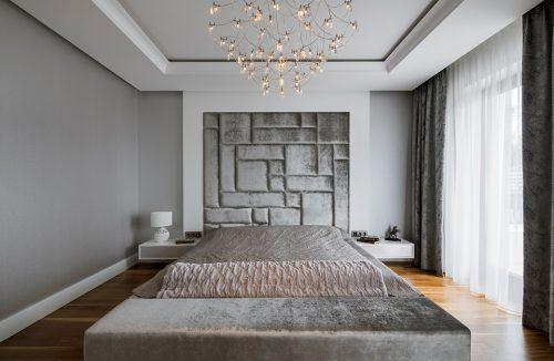 elegancka biało szara sypialnia z dużym łóżkiem ze srebrną narzuta pod wyjątkowym żyrandolem