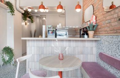 bar lodziarni z małymi prostokątnymi kafeleczkami oraz wiszącymi pomarańczowymi lampami w wnętrzu z lekko różowymi krzesłami