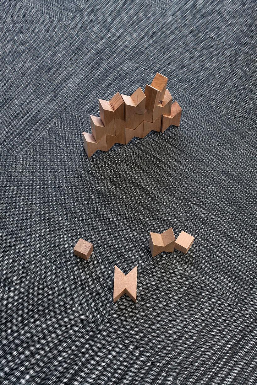 szara wykładzina Fitnice Floor od Newmor zleżącymi na niej drewnianymi klockami