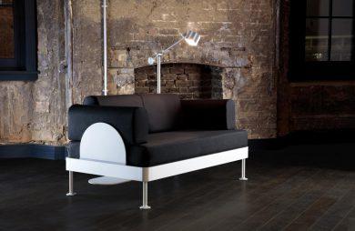 brązowa sofa z białą konstrukcją na tle ceglanej ściany