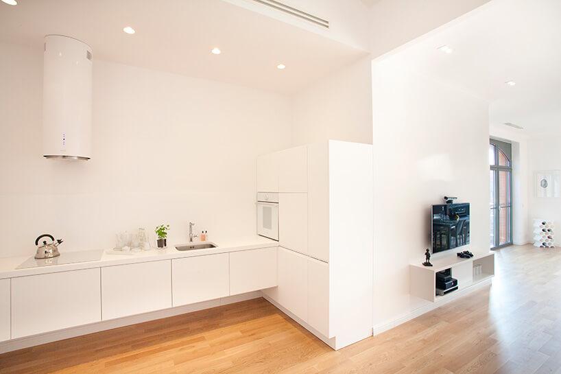 biały aneks kuchenny obok salonu