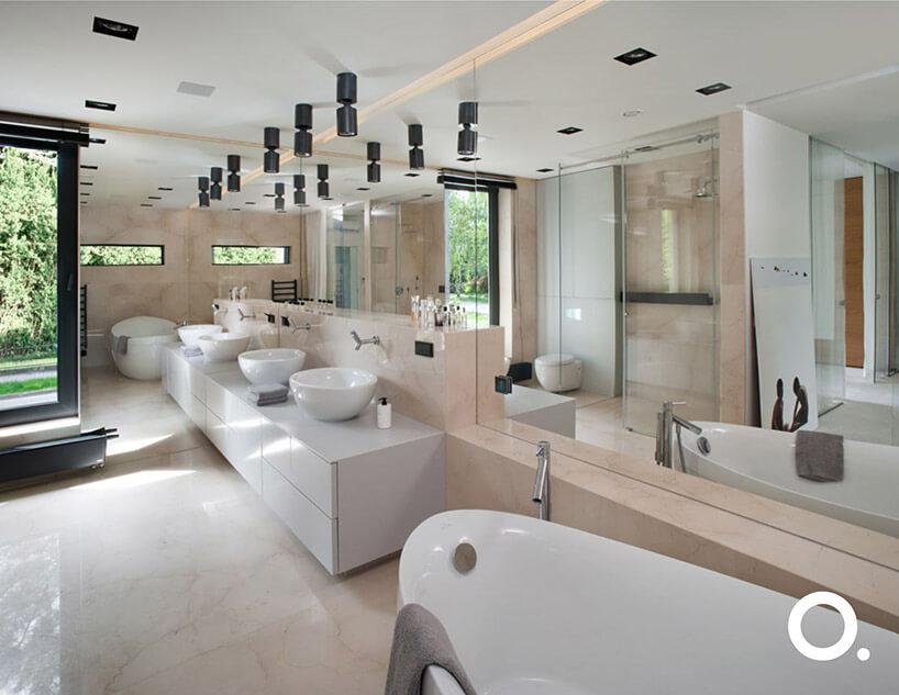 duża jasna łazienka zdwoma umywalkami ilustrem na ścianie