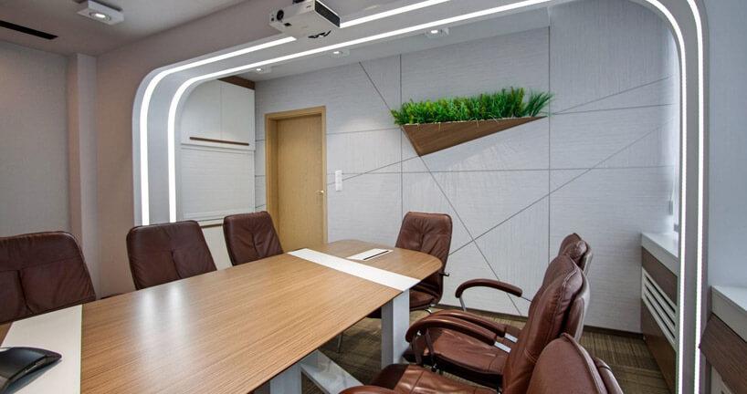 brązowe krzesła wsali zdoniczką na ścianie
