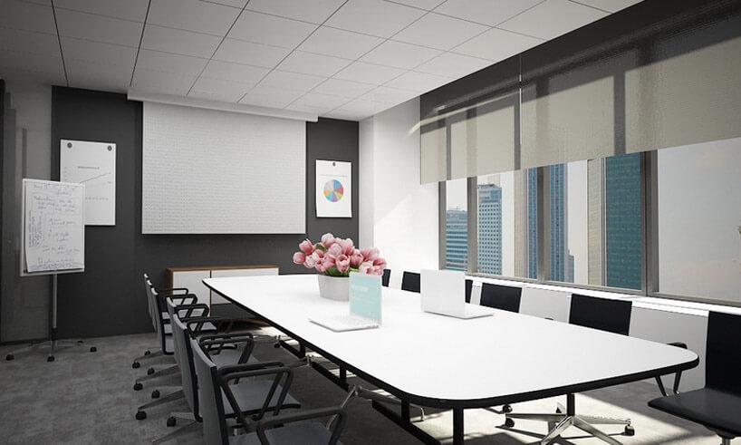 biały stół zczarnymi krzesłami wdużej jasnej sali