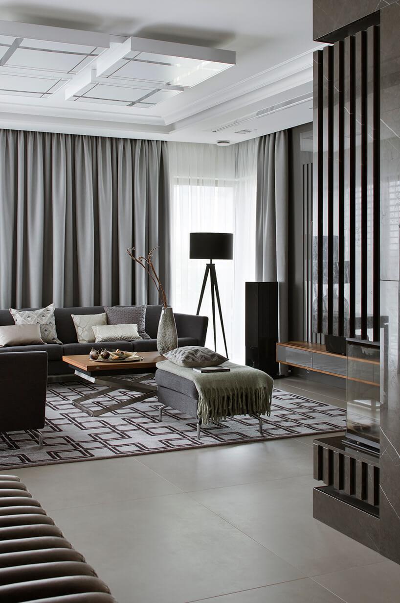 elegancki apartament Hola Design znagrodą EPA 2019-2020 szara narożna sofą przy stoliku zdrewnianym kwadratowym blatem na tle szarych zasłon