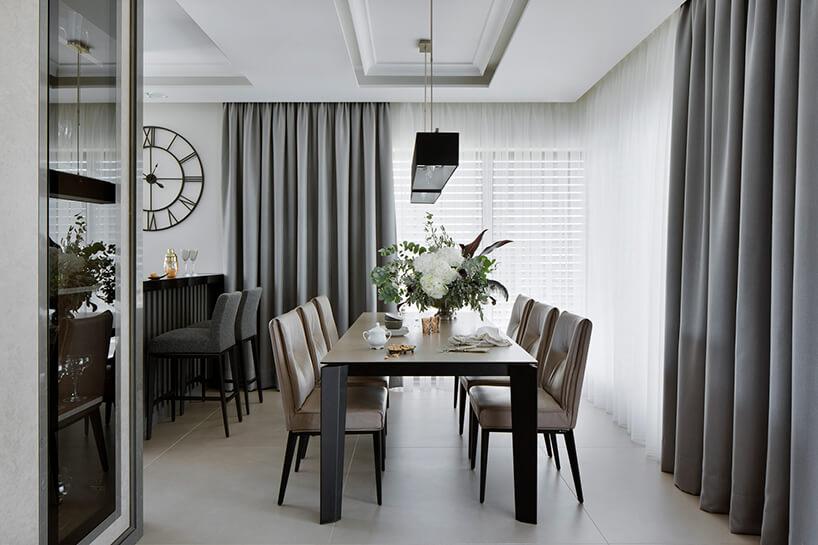 elegancki apartament Hola Design znagrodą EPA 2019-2020 duży stół zjasnym blatem iciemnymi nogami zsześcioma brązowymi krzesłami