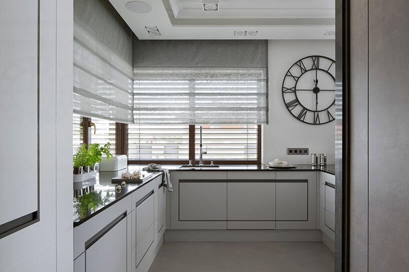 elegancki apartament Hola Design znagrodą EPA 2019-2020 biała kuchnia zciemnym blatem iciemnym akcentami we frontach