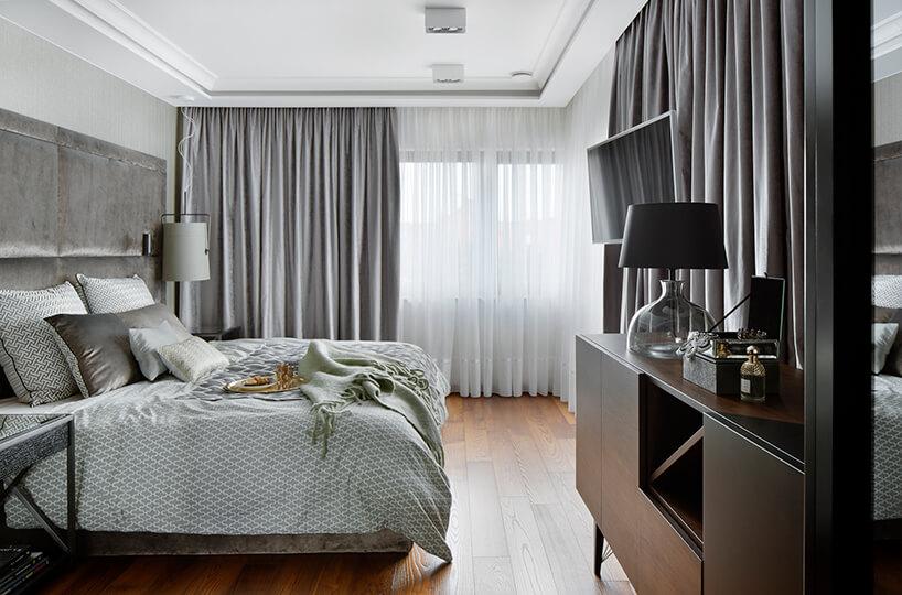 elegancki apartament Hola Design znagrodą EPA 2019-2020 przestronna sypialnia zbrązową drewnianą podłogą zdużym szarym łóżkiem ociemną brązową szafką