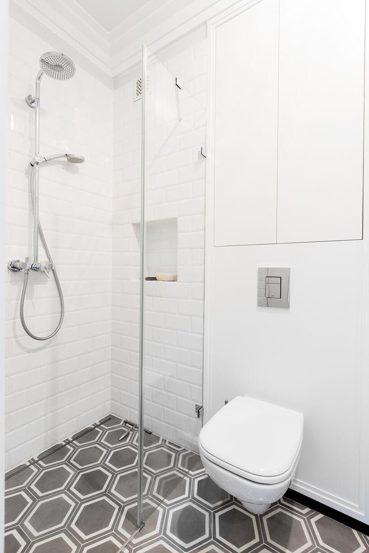 biała łazienka zdużym prysznicem iczarną podłogą