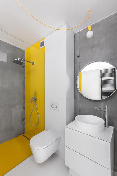 mała łazienka wszaro-białych kolorach zżółtym akcentem pod prysznicem