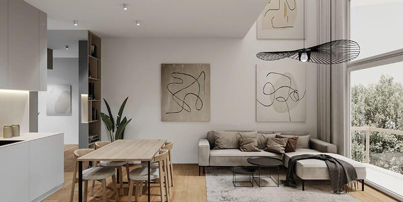 duże jasne pomieszczenie zbeżowymi ścianami istołem oraz krzesłami zdrewna przy białej kuchni