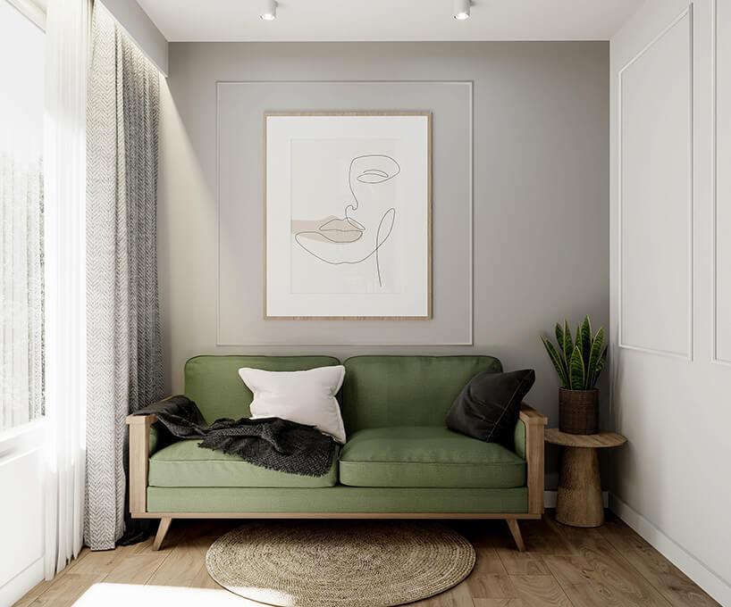 ściany ze sztukaterią oraz nowoczesnym obrazem przy zielonej drewnianej kanapie zbiałą poduszką