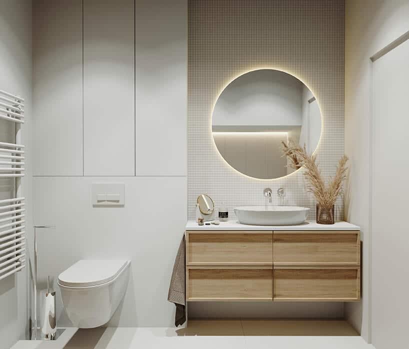 biała wisząca toaleta przy drewnianej szafce zbiałym blatem zumywalką izłotą wylewką