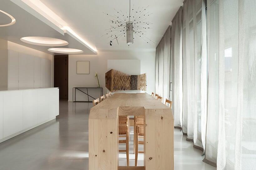 salon zbiałą aranżacją oraz długimi zasłonami oraz nietypowym wysokim drewnianym stołem