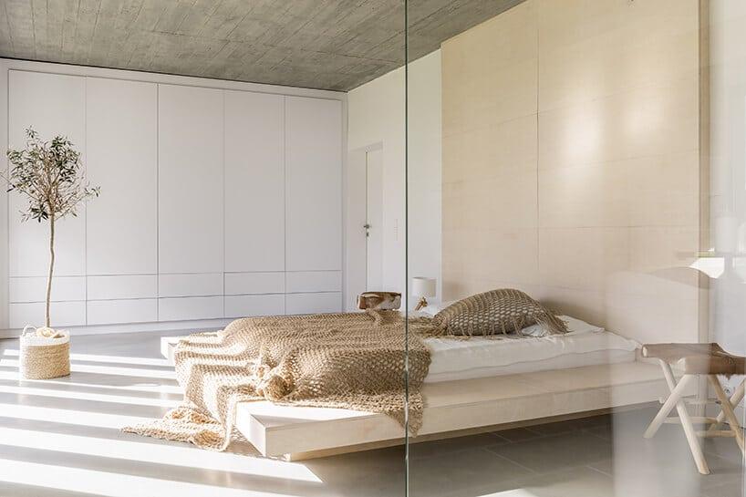 minimalistyczna sypialnia zlewitującym łóżkiem wsypialni zbeżem oraz bielą oraz szkłem