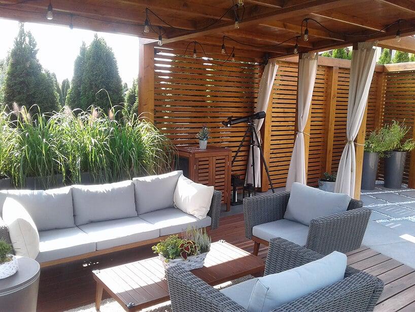 miejsce do odpoczynku zkanapami oraz fotelem wcieniu ogrodu zzadaszeniem