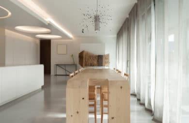 salon z białą aranżacją oraz długimi zasłonami oraz nietypowym wysokim drewnianym stołem
