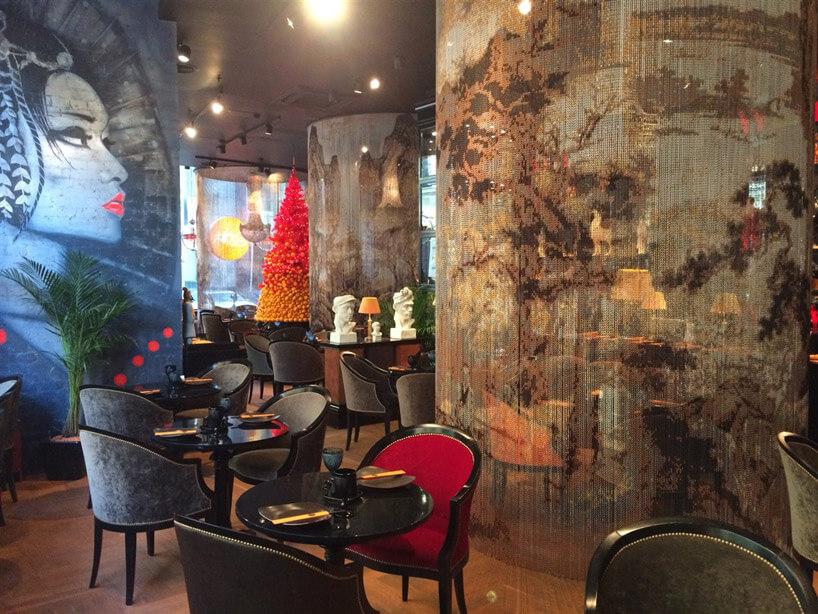 szaro czerwone fotele przy ścianie zmuralem kobiety
