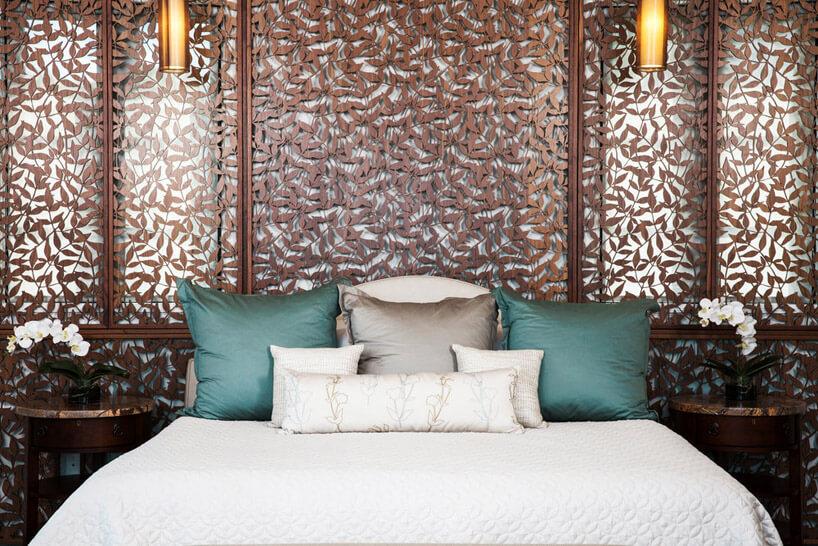 łóżko zbiałą narzutą zzielonymi poduszkami
