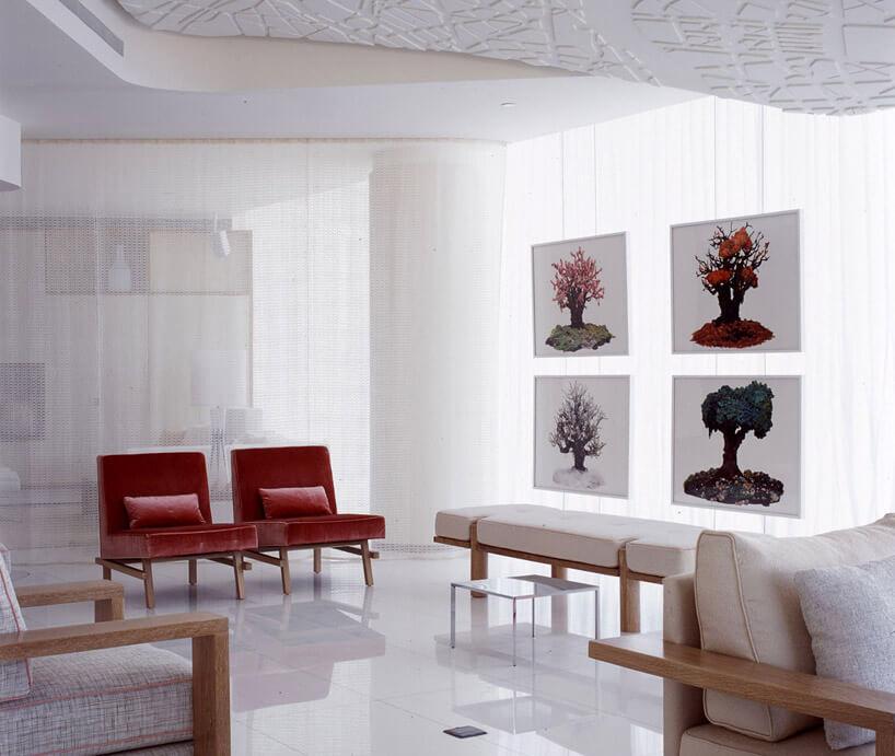 nowoczesny salon zczerwonymi fotelami iobrazami postaci