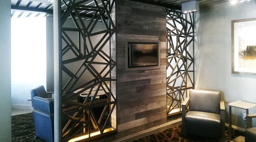 telewizor powieszony na drewnianej ścianie zmetalową konstrukcją