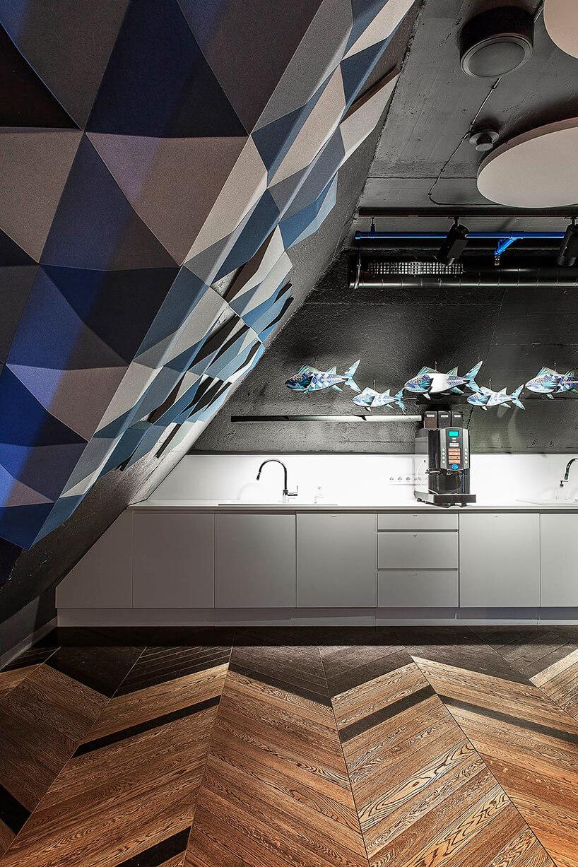 przestrzęń biurowa zdrewnianą podłogą pochyloną ścianą zpanelami 3D