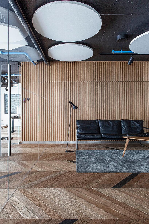 nowoczesna przestrzeń biurowa zdrewnianą podłogą idużą ścianą zdrewna jako tło czarnej sofy skórzanej