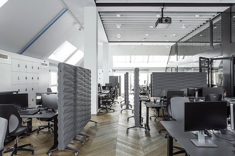 nowoczesna przestrzeń biurowa open space zszarym wystrojem zmobilnym ściankami dsziałowymi