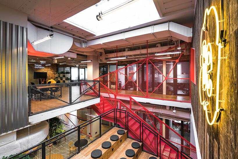 przestrzeń coworkingowa Brain Embassyduże żółte logo oraz czerwone metalowe schody