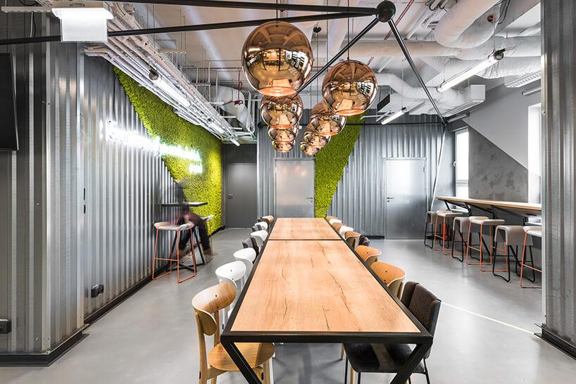 przestrzeń coworkingowa Brain Embassy duży stół zkrzesłami pod wyjątkowymi lampami zdużymi złotymi kloszami