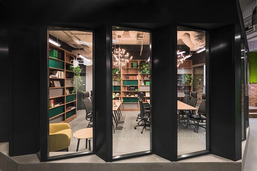 przestrzeń coworkingowa Brain Embassy zwydzieloną częścią konferencyjną zdrewnianymi stołami iczarnymi krzesłami biurowymi