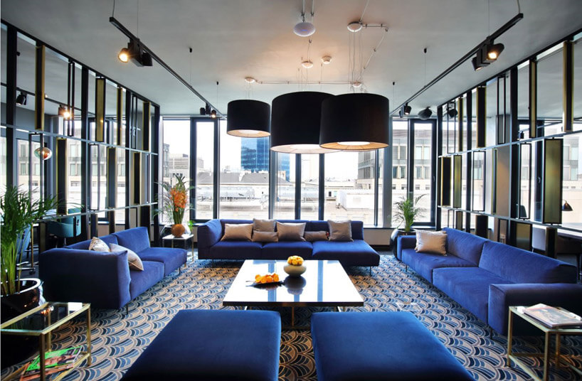 niebieskie fotele ikanapy wdużym pomieszczeniu zdużymi oknami ilampami