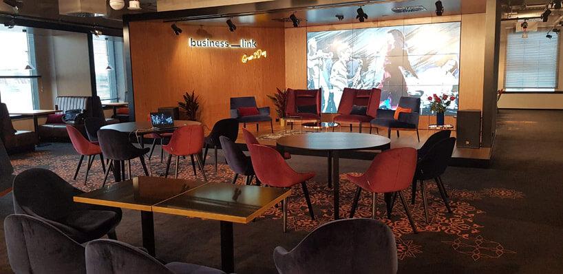 sala konferencyjna zpomarańczowymi iczarnymi krzesłami