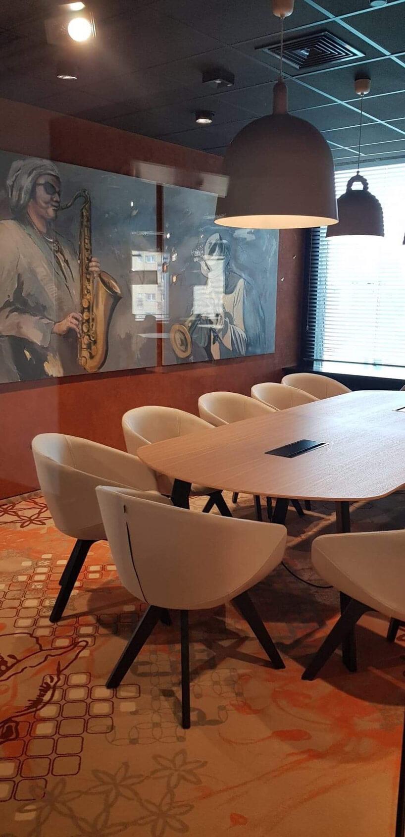 beżowe fotele na ciemnych nogach przy dużym stole wsali zobrazem