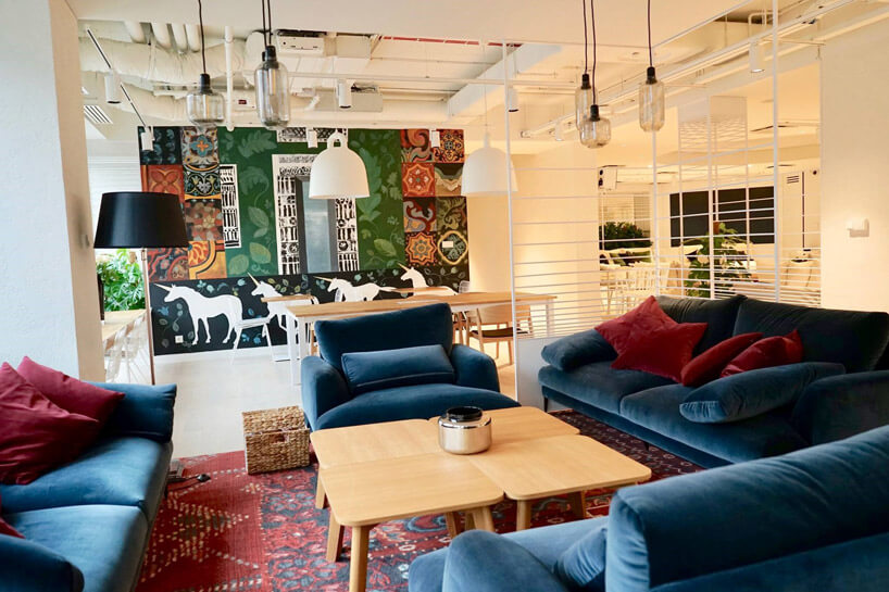 pomieszczenie zdużą ilością lamp oraz fotelami ikanapami wciemno niebieskim koloże