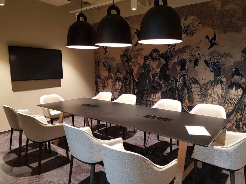 trzy duże ciemne lampy zjasnym wnętrzem nad brązowym dużym stołem