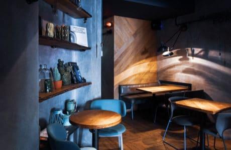 wnętrze restauracji ze stolikami z drewna oraz krzesłami w kolorze niebieskim oraz czarnym skózanym
