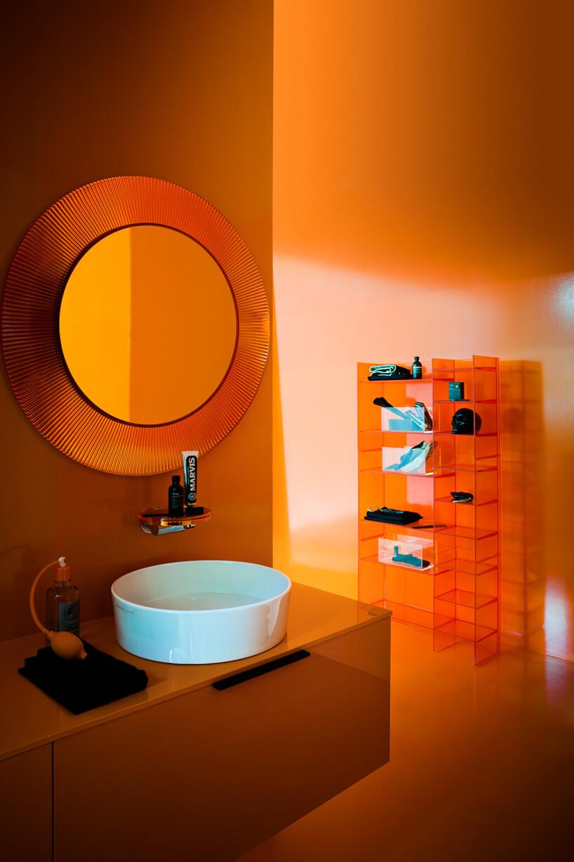 łazienka zpomarańczową przeźroczystą szafką, regałem irama lustra od Kartell by Laufen