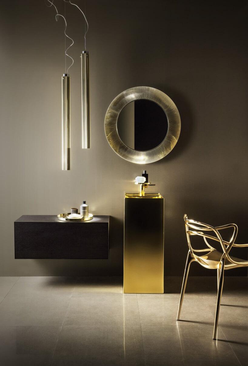 elegancka aranżacja łazienki ze złotą umywalką pod okrągłym lustrem zgrubą ramą od Kartell by Laufen