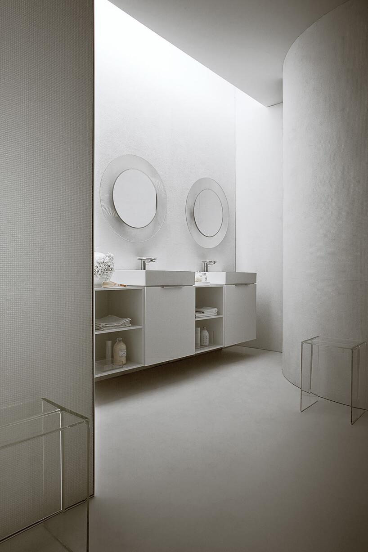 elegancka aranżacja białej łazienki zdwoma lustrami zszeroką przeźroczystą ramą idwoma stołkami od Kartell by Laufen