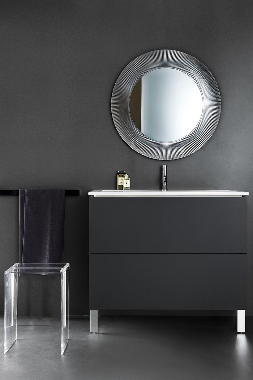 elegancka ciemna łazienka zprzeźroczystym stołkiem iwiszącym nad czarną szafką lustrem zgrubą transparentną ramą od Kartell by Laufen
