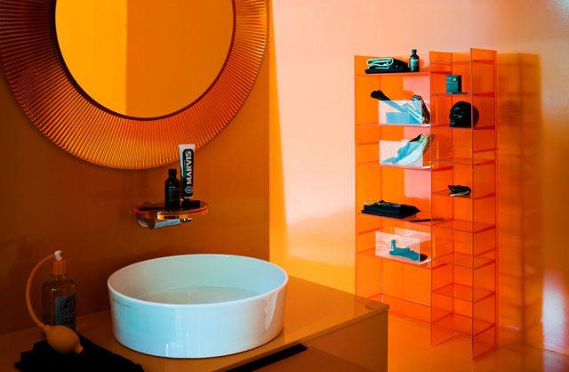 łazienka z pomarańczową przeźroczystą szafką, regałem i rama lustra od Kartell by Laufen