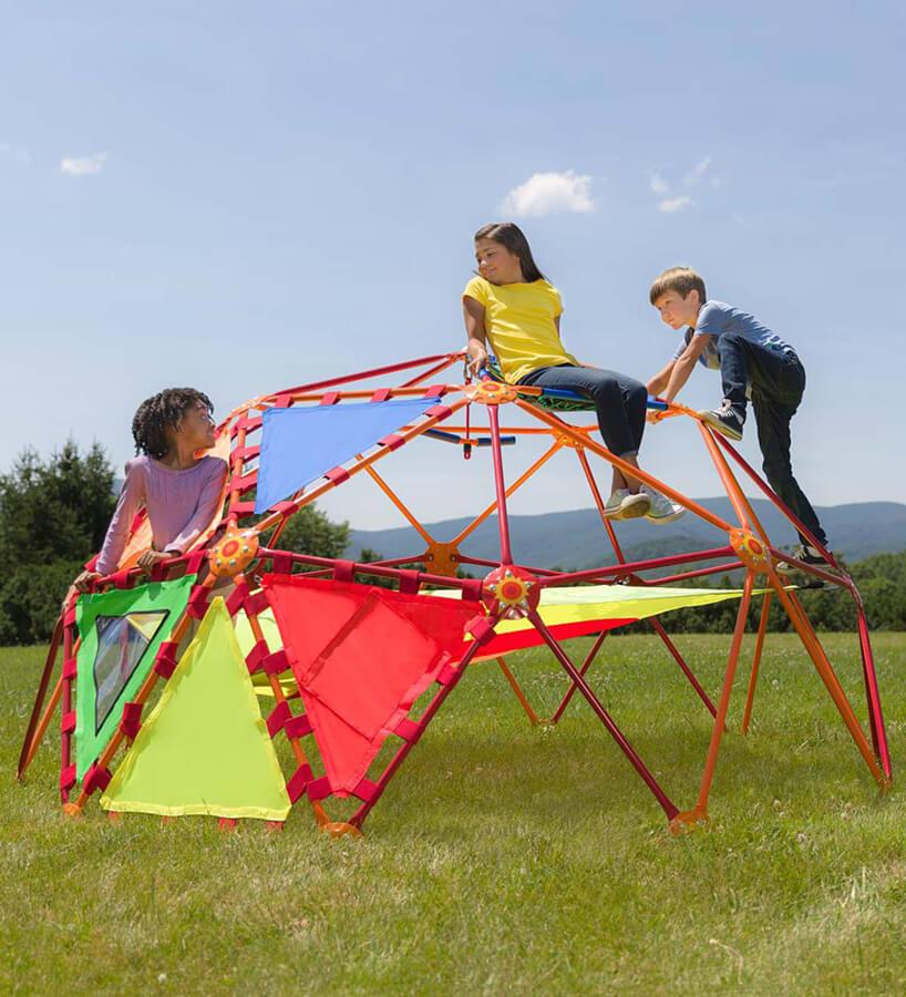 trójka dzieci podczas zabawy na czerwonym małpim gaju