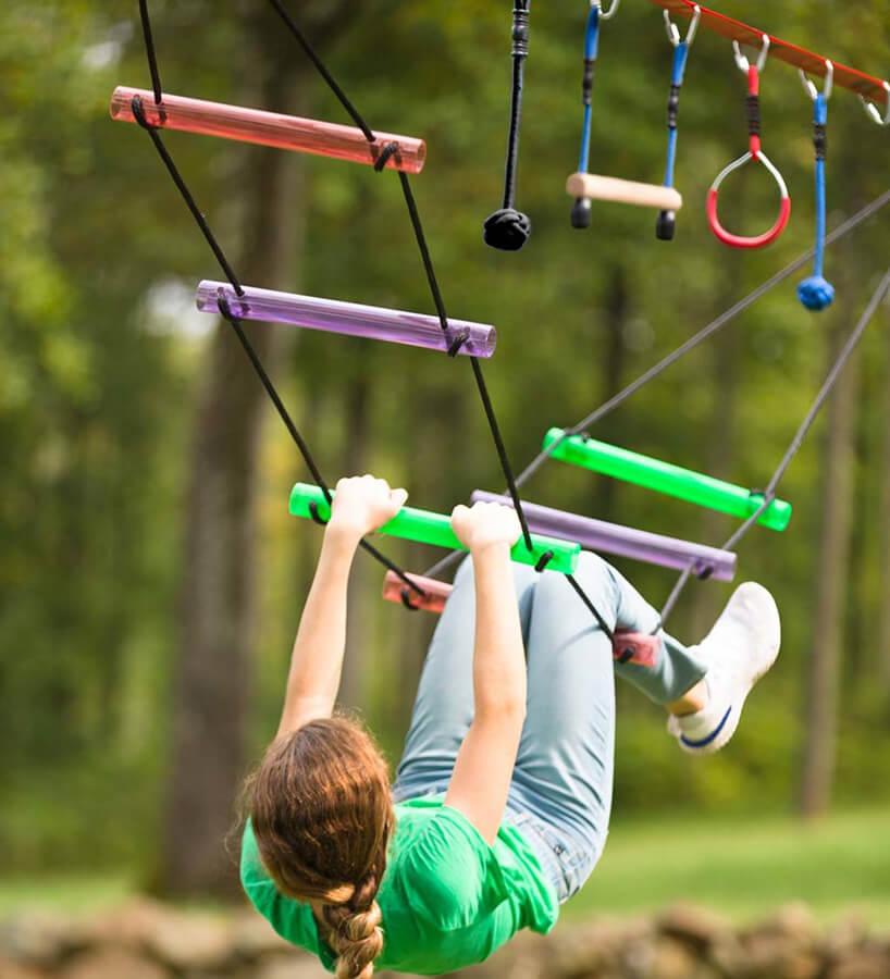 dziecko podczas zabawy na zawieszonych poziomo drabinkach
